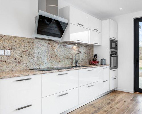 Platsbyggt kök med luckor i vitt högblankt