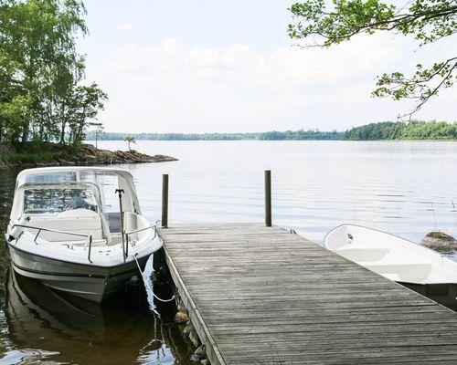Brygga med motorbåt och roddbåt (ingår i köpet)