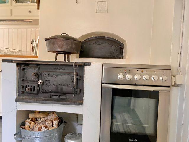 Vedspis och spis med häll och ugn i köket